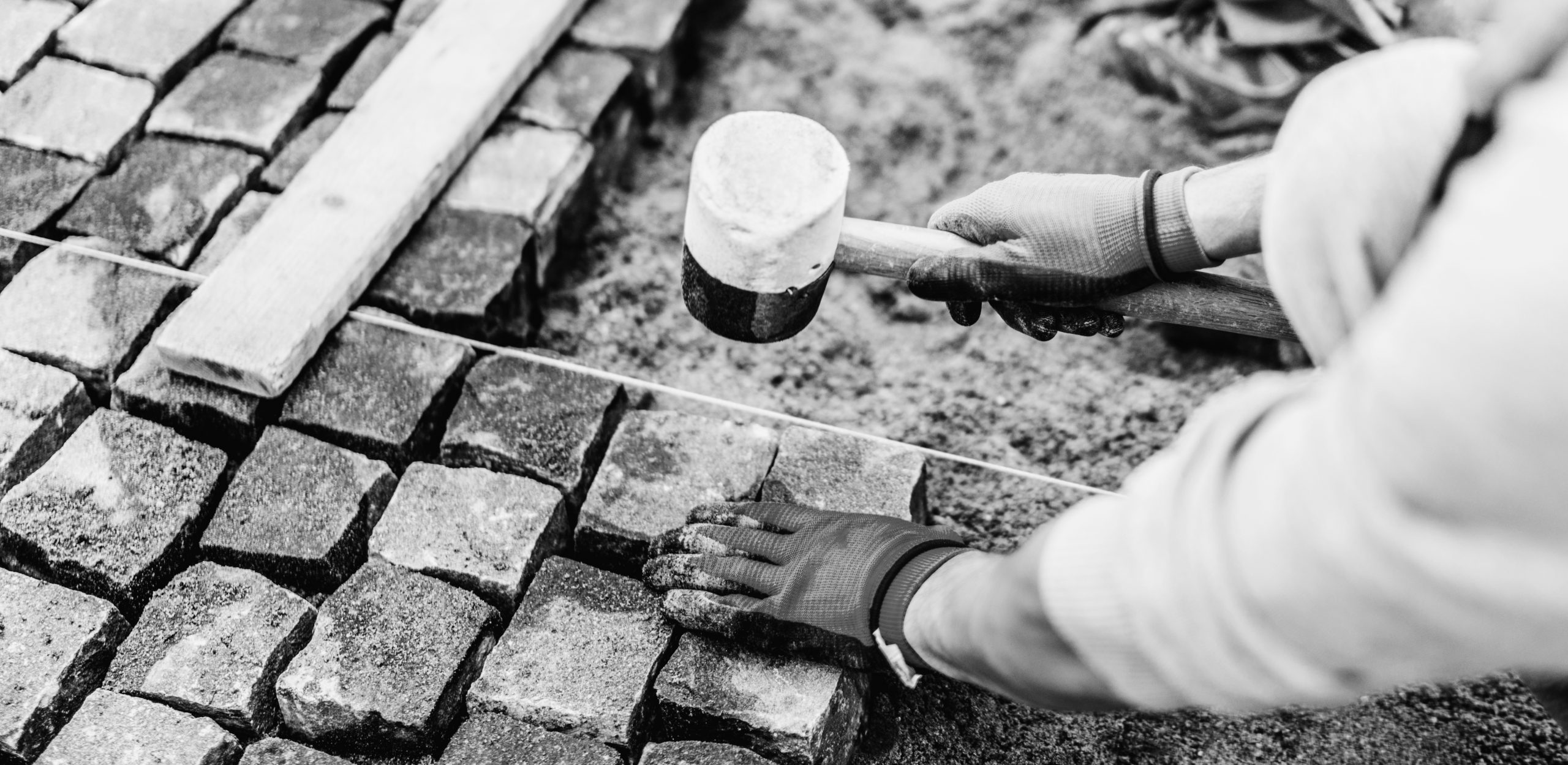 Construction worker installing stone on pavement. Details of construction site