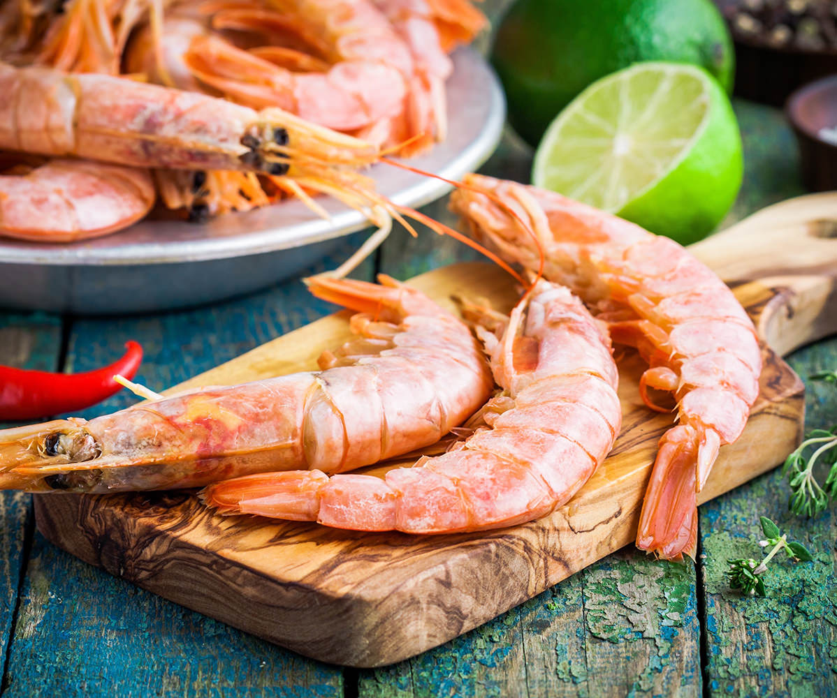 fresh raw prawns on a wooden cutting board with salt, pepper, lime on a rustic table
