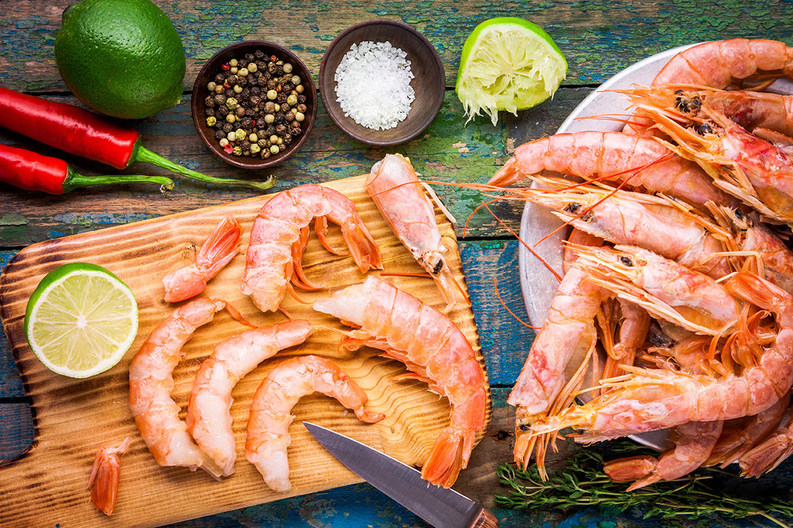 peeled fresh shrimps on wooden board with salt, chili pepper, lime