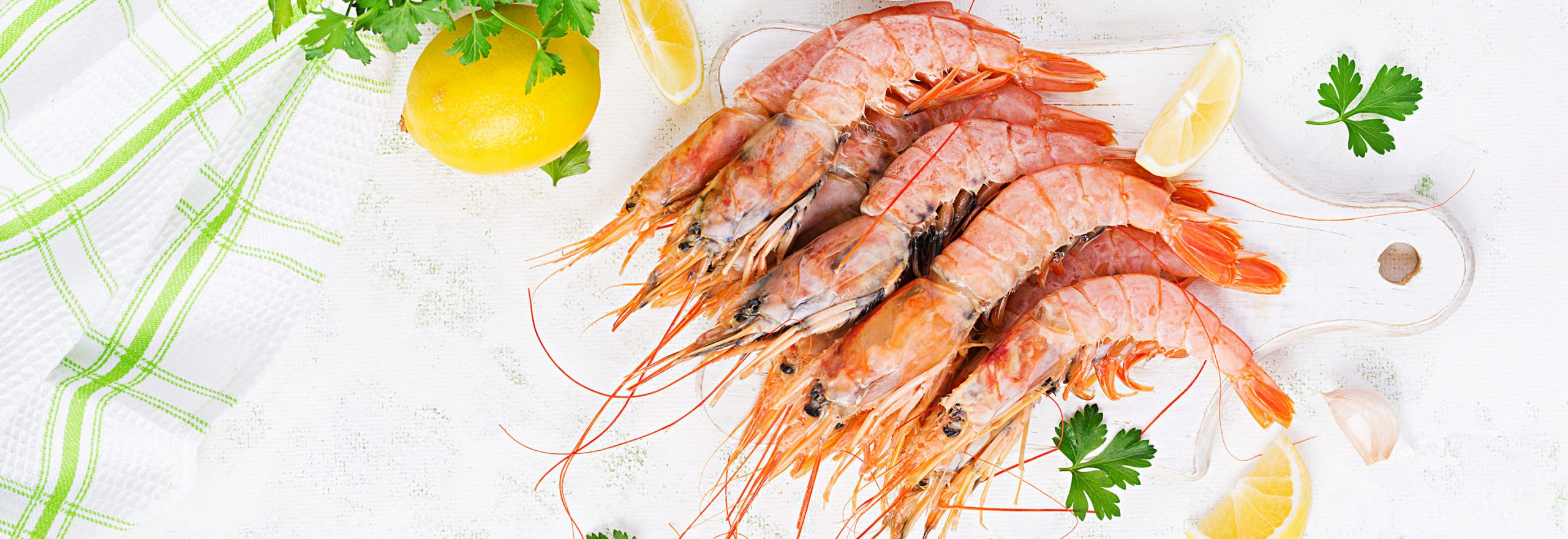 Raw wild Argentinian red shrimps/prawns  and ingredients for cooking. Delicious food. Keto / Paleo Diet. Top view, banner